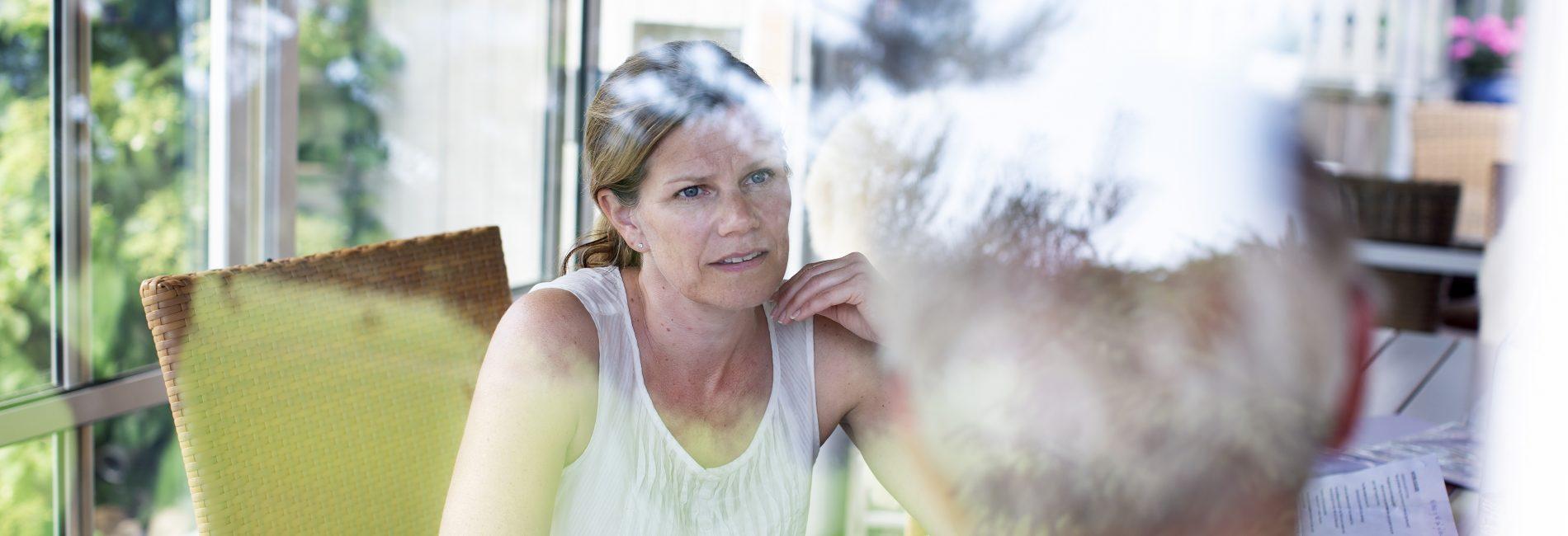 Kvinne snakker med mann bak vindu. Foto.
